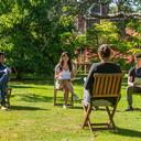 image of students sitting outside speaking to a tutor