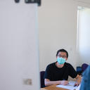 image of a young man wearing a face mask being taught by an older man wearing a face mask